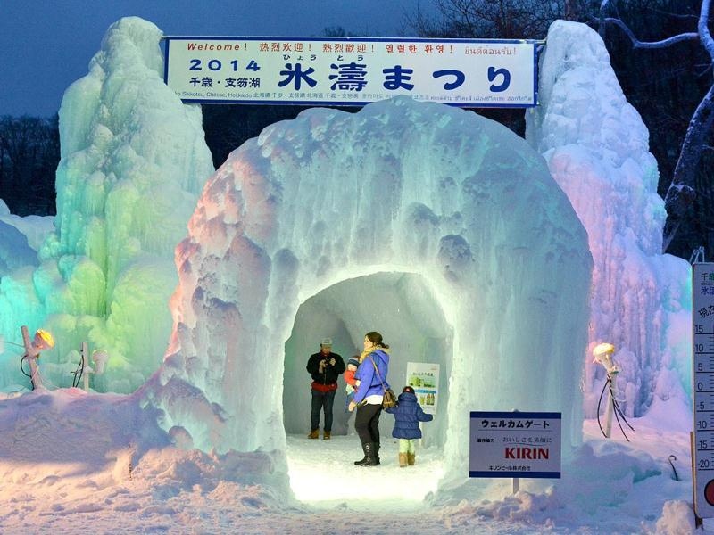 Visitors take picture at a welcome gate of the annual ice festival. (AFP)