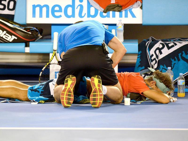 A trainer works on the back of Rafael Nadal of Spain between games against Stanislas Wawrinka of Switzerland in the men's singles final of the 2014 Australian Open in Melbourne. (AFP Photo)