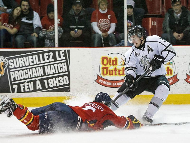 Simon Tardif-Richard of the Gatineau Olympiques controls the puck as Alexandros Soukamis of the Acadie-Bathurst Titan dives to block. (AFP Photo)
