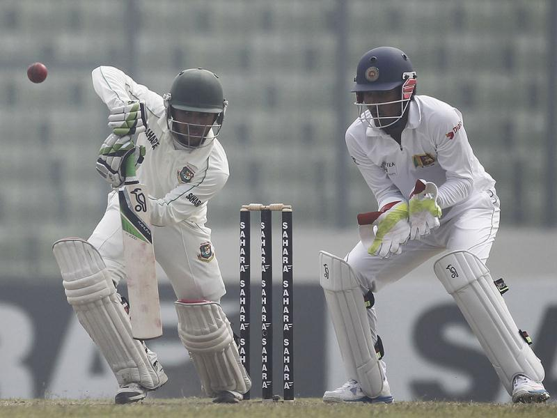 Bangladesh's Mominul Haque plays a ball as Sri Lanka's wicketkeeper Dinesh Chandimal (R) looks on during the fourth day of their first Test in Dhaka. (Reuters Photo)