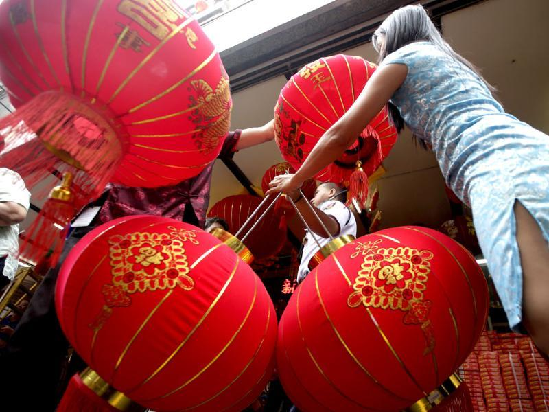 A saleswoman holds Chinese lanterns for a customer in front of a department store on the eve of Chinese New Year at Manila's Chinatown district of Binondo in the Philippines. (AP photo)