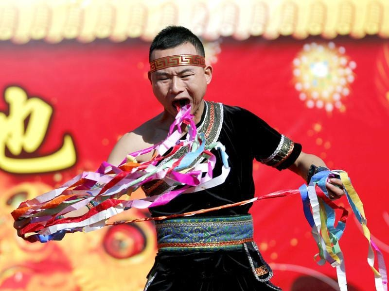 A man pulls ribbons from his mouth as he performs a feat of his strength during the opening of the temple fair for Chinese New Year celebrations at Ditan Park, also known as the Temple of Earth, in Beijing.