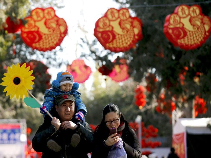 A family walks underneath Chinese New Year decorations during the opening of the temple fair for the Chinese New Year celebrations at Ditan Park, also known as the Temple of Earth, in Beijing. (Reuters photo)