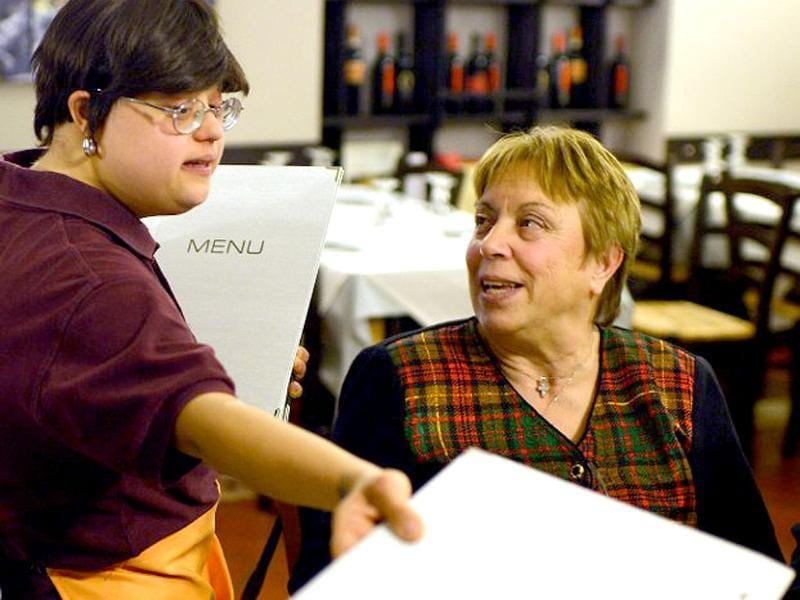 Emanuela Annini, a young women with Down syndrome, works in the restaurant 'Locanda dei Sunflowers' in Rome. This restaurant is born with the overall objective of promoting the employment of people with Down syndrome, ennobling and giving dignity to the person through an individual path, training and job placement. (AFP photo)