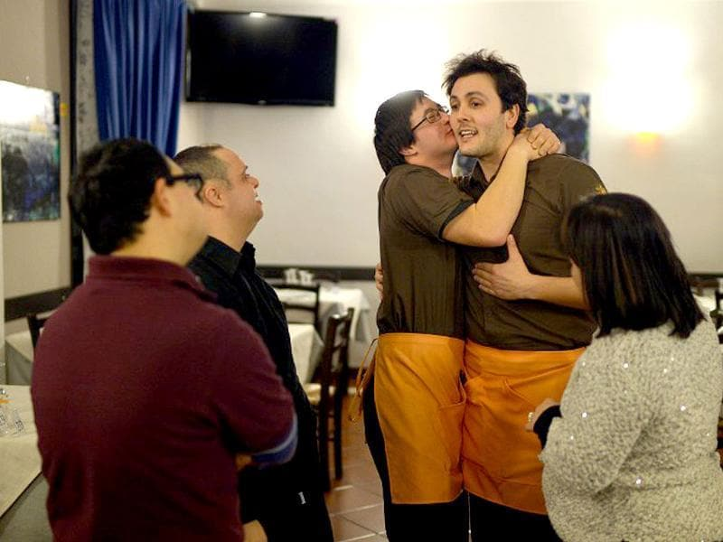 Simone Ippoliti (C-left), a young man with Down syndrome, kisses his chief (R) in the restaurant 'Locanda dei Sunflowers' where he works in Rome. (AFP photo)