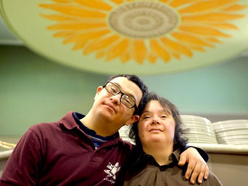 Viviana Polselli (R) and Alessandro Giusto, young people with Down syndrome, pose as they work in the restaurant 'Locanda dei Sunflowers' in Rome. (AFP photo)