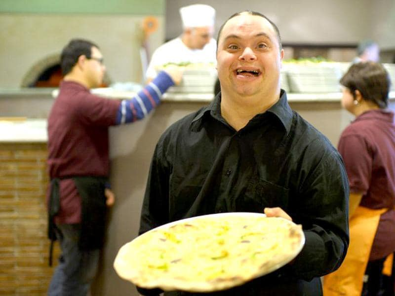Ettore Tommasetti, a young man with Down syndrome, works in the restaurant 'Locanda dei Sunflowers' in Rome. (AFP photo)