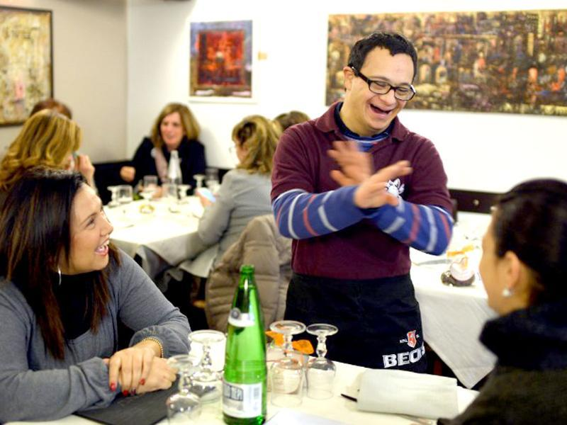 Alessandro Giusto (C) a young man with Down syndrome, jokes with clients as he works in the restaurant 'Locanda dei Sunflowers' in Rome. (AFP photo)