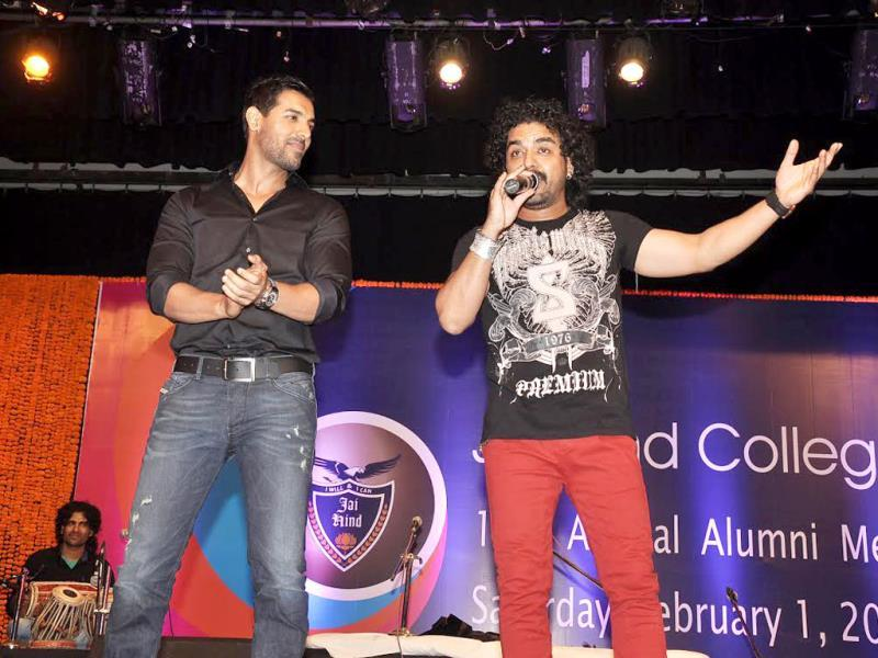 John Abraham looks on as singer Toshi Sabri performs at the meet.