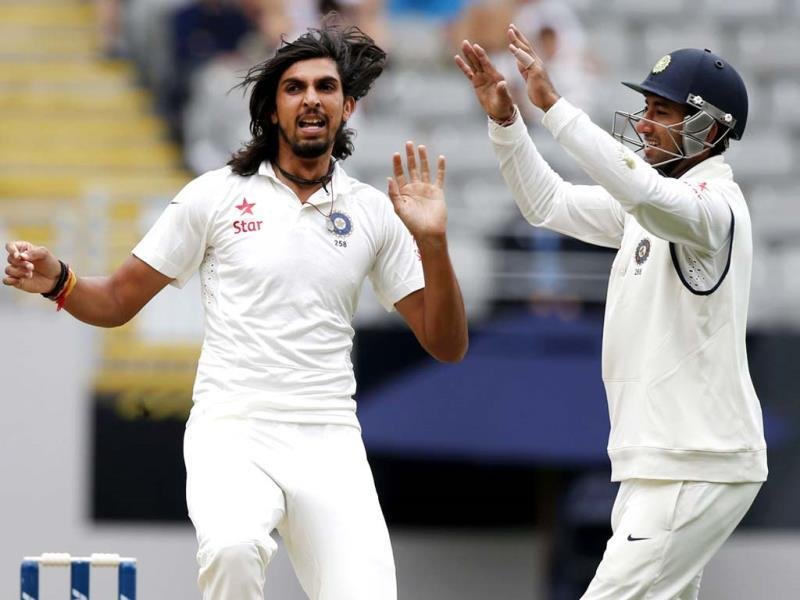 Ishant Sharma (L) celebrates with team mate Cheteshwar Pujara (R) after dismissing New Zealand's Hamish Rutherford on day one of the Test at Eden Park in Auckland. (Reuters Photo)