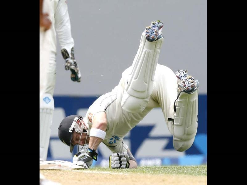 New Zealand's Brendon McCullum goes for a tumble while trying to make his crease on day one of the first Test against India at Eden Park in Auckland. (Reuters Photo)