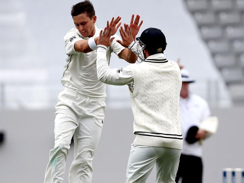 Trent Boult of New Zealand celebrates with Hamish Rutherford (R) the wicket of Cheteshwar Pujara during day two of the first Test at Eden Park in Auckland. (AFP Photo)