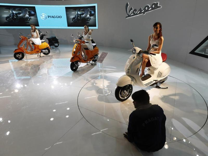 Automotive firms tutor the girls about their company, the vehicles and other details. Models sit on scooters at the Vespa pavilion as a worker cleans the floor during the 12th Auto Expo 2014 in Greater Noida, on the outskirts of New Delhi. (Reuters)