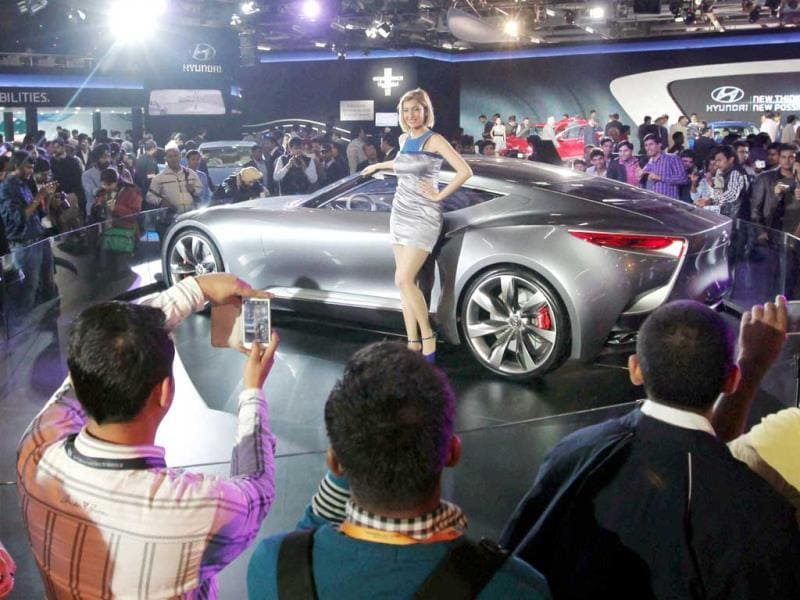 Cars or models? People crowd around a car and click pictures of the model flanking it (PTI photo)