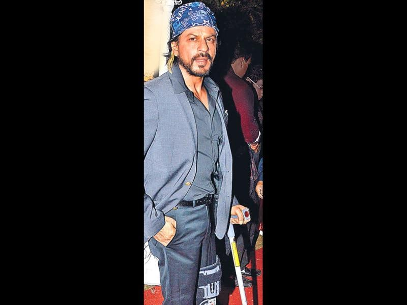 Shahrukh Khan, who hurt himself while shooting for his upcoming film Happy New Year, attended the reception of Ahana Deol wearing a funky knee cast. (HT Photo)