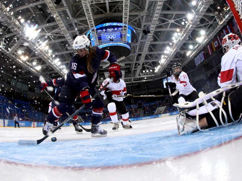 US Kelli Stack (L) misses a shot in front of Switzerland's goalkeeper Florence Schelling during the Women's Ice Hockey Group A match USA vs Switzerland at the Shayba Arena during the Sochi Winter Olympics. (AFP Photo)