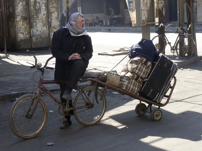 A man sits on a bicycle with his belongings at the besieged al-Yarmouk camp, south of Damascus. (Reuters)