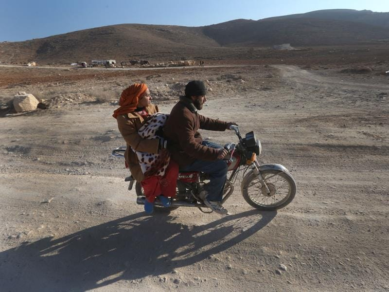 A Syrian man with his wife and child ride a motorcycle as they flee from Yabroud, the last rebel stronghold in Syria's mountainous Qalamoun region, on their way to the Lebanese-Syrian border town of Arssal, in eastern Lebanon. In Lebanon, preparations were underway to receive more Syrians fleeing the area. Syrian warplanes pounded a rebel-held town near the Lebanese border, activists said, as opposition leaders in Geneva called on Russia to put pressure on the government to prevent the faltering peace negotiations from collapsing. (AP Photo)