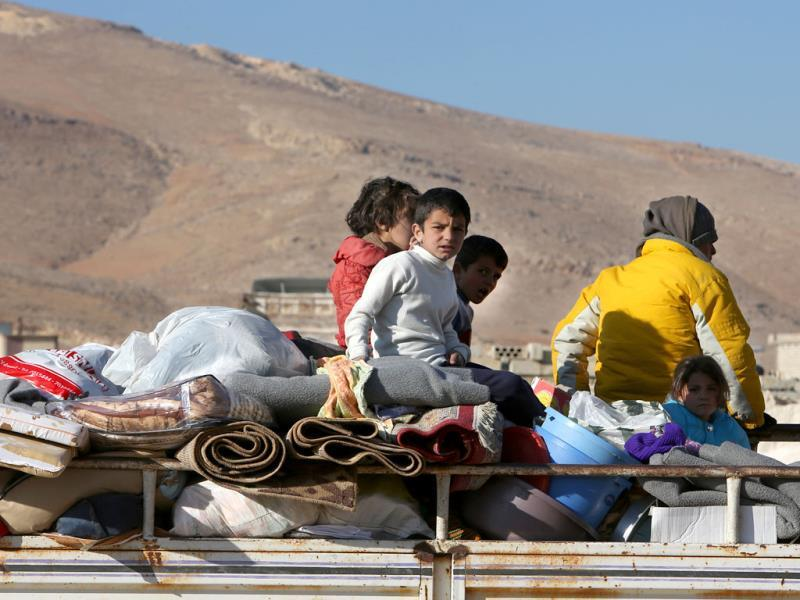 Syrian children who fled from Yabroud, the last rebel stronghold in Syria's mountainous Qalamoun region, sit on top of a truck with their belongings, as they arrive at the Lebanese-Syrian border town of Arssal, in eastern Lebanon. (AP Photo)