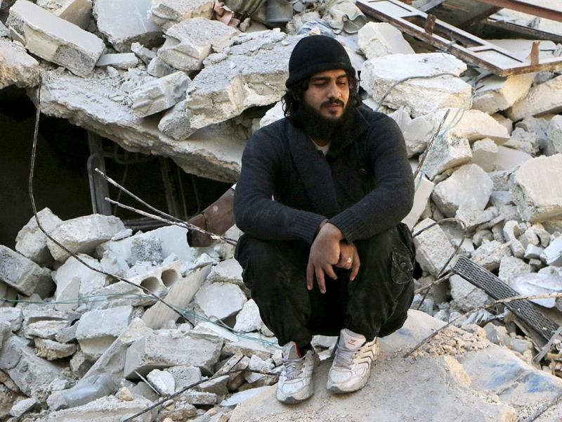 A man sits on the rubble of collapsed buildings at a site hit by what activists said was a barrel bomb dropped by forces loyal to Syria's President Bashar al-Assad in the al-Myassar neighbourhood of Aleppo. (Reuters)