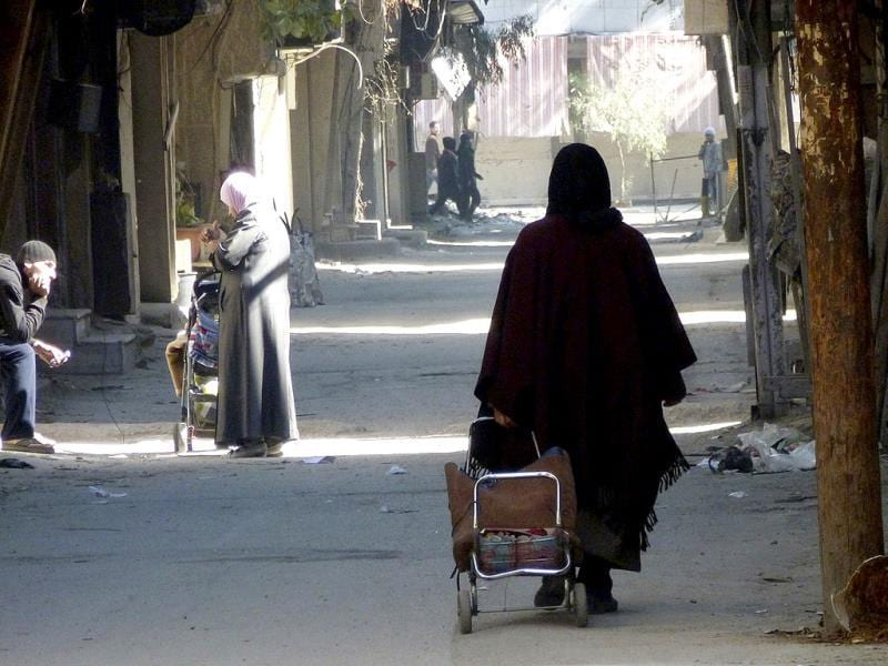 A woman walks with her bag along a street at the besieged al-Yarmouk camp, south of Damascus. (Reuters)