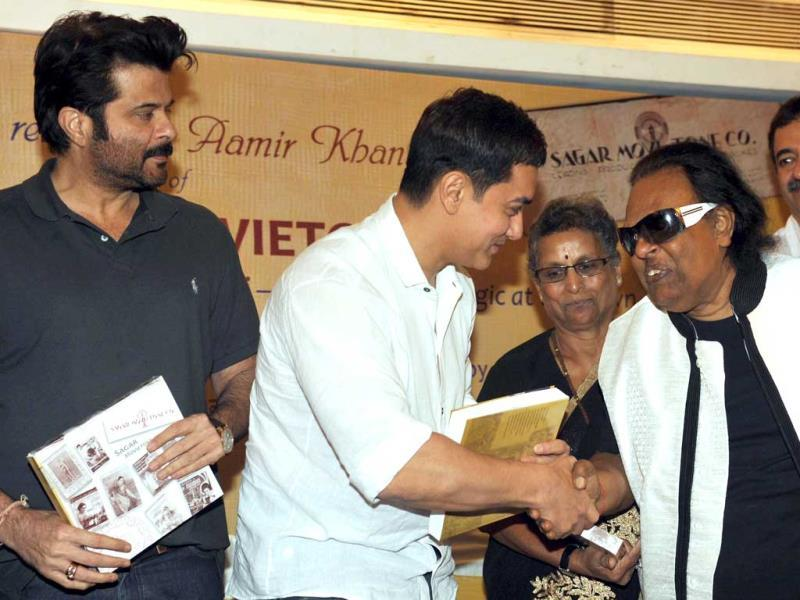 Aamir Khan greets music director and singer Ravindra Jain as Anil Kapoor looks on during the launch of the book Sagar Movietone, written & compiled by Biren Kothari in Mumbai on February 11, 2014. (AFP Photo)