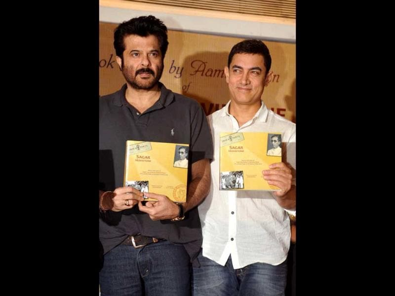 Anil Kapoor and Aamir Khan pose for the shutterbugs during the launch of Sagar Movietone, written & compiled by Biren Kothari in Mumbai. (AFP Photo)