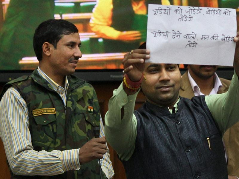 A member shows a placard in the Delhi Assembly during its special session called for anti-corruption Jan Lokpal Bill, in New Delhi (PTI photo)