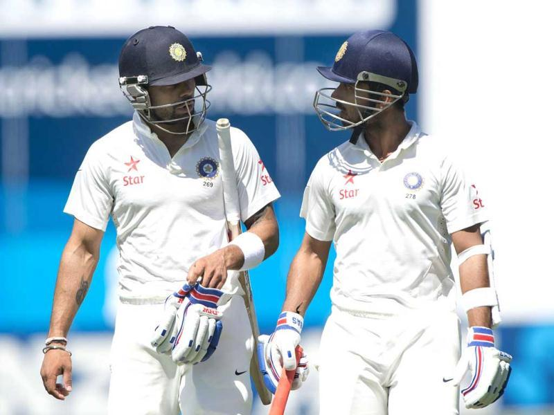 Ajinkya Rahane (R) with team mate Virat Kohli walk off the field for lunch during Day 2 of the 2nd Test against New Zealand at the Basin Reserve in Wellington. (AFP Photo)