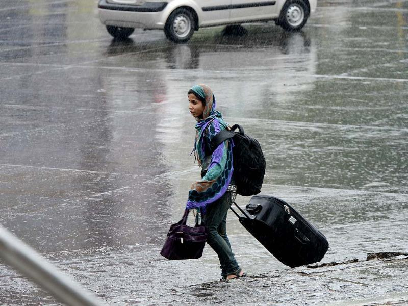 A woman drags her bag accross the street during unexpected rains in Mumbai (Kunal Patil/HT)