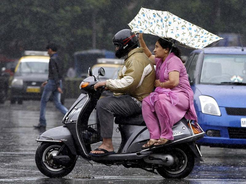 Sudden rainfall in Mumbai caught may unaware, including this couple on a scooter (Kunal Patil/HT)