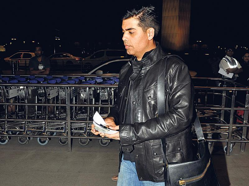 Karan Johar heads to the check-in counter at the Mumbai airport.