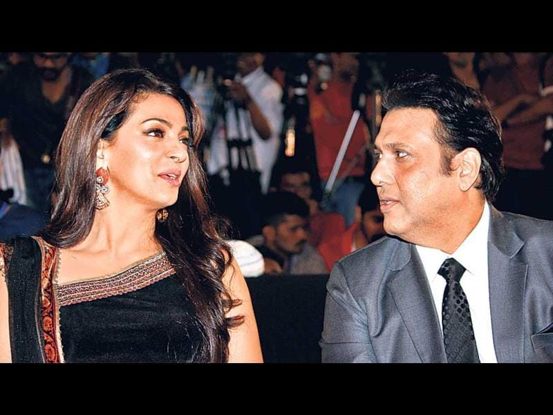 Juhi Chawla and Govinda engrossed in a conversation at an event.