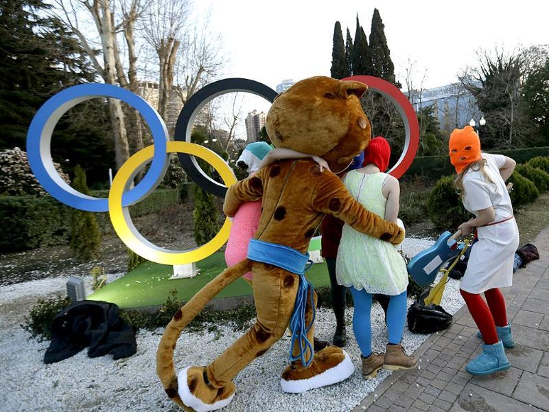 The Sochi mascot accompanies Pussy Riot group after they were attacked to safety (AP photo)
