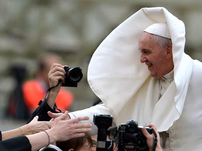 Pope Francis salutes the crowd as as gust of wind blows his mantle in St Peter's square at the Vatican. (AFP photo)