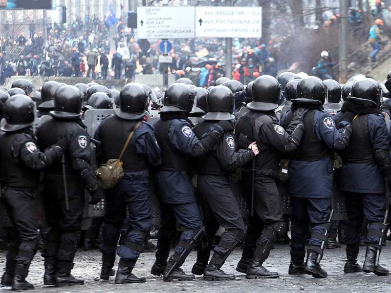 Riot police face anti-government protesters during clashes central Kiev. Ukraine's brittle truce shattered in fierce clashes between baton-wielding protesters and riot police. (AFP photo)