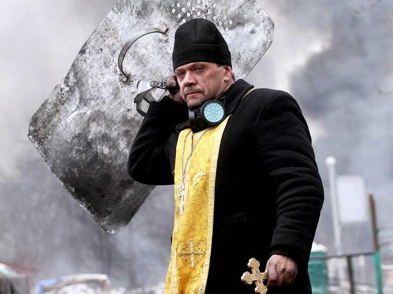 A priest holds a cross and shield during clashes betwwen anti-government protesters and riot police in central Kiev. (AFP photo)