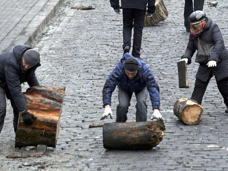 Anti-government protesters push logs to build barricades during clashes with riot police in the Independence Square in Kiev. (Reuters)