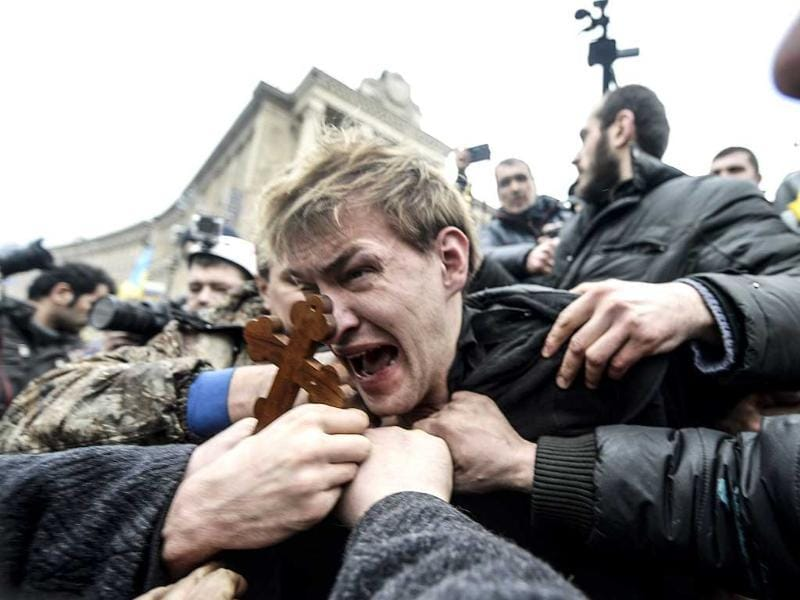 An alleged sniper (C) and member of the pro-government forces is beaten by anti-government protestors in Kiev. (AFP Photo)
