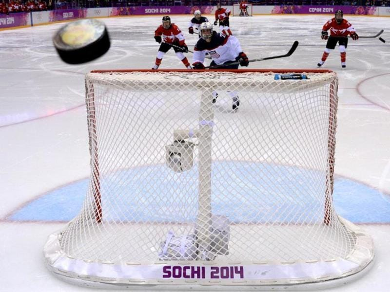 US Kacey Bellamy (C) eyes the puck flying over the net after scoring during the Women's Ice Hockey Gold Medal Game between Canada and USA at the Bolshoy Ice Dome during the Sochi Winter Olympics on February 20, 2014. AFP PHOTO