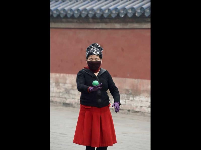 This picture taken on February 24, 2014 shows a woman wearing a mask exercizing in a park in haze-covered Beijing. (AFP Photo)