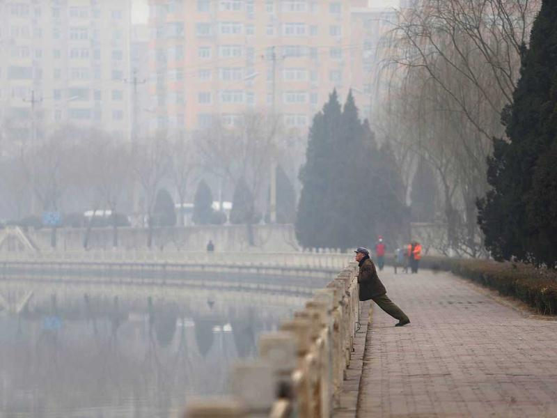 Picture shows a man (R) exercizing in haze-covered Beijing. (AFP photo)