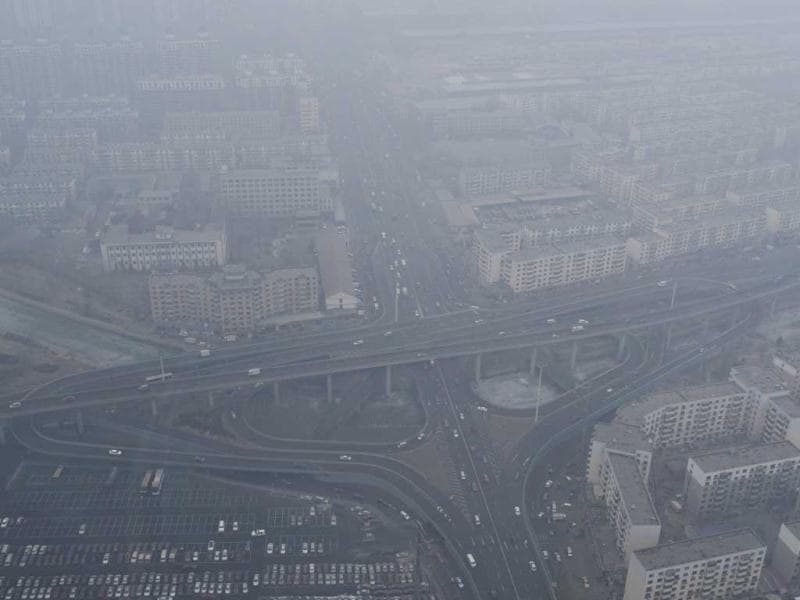 Vehicles travel on a viaduct next to residential buildings amid thick haze in Shenyang, Liaoning province February 24, 2014. (Reuters Photo)