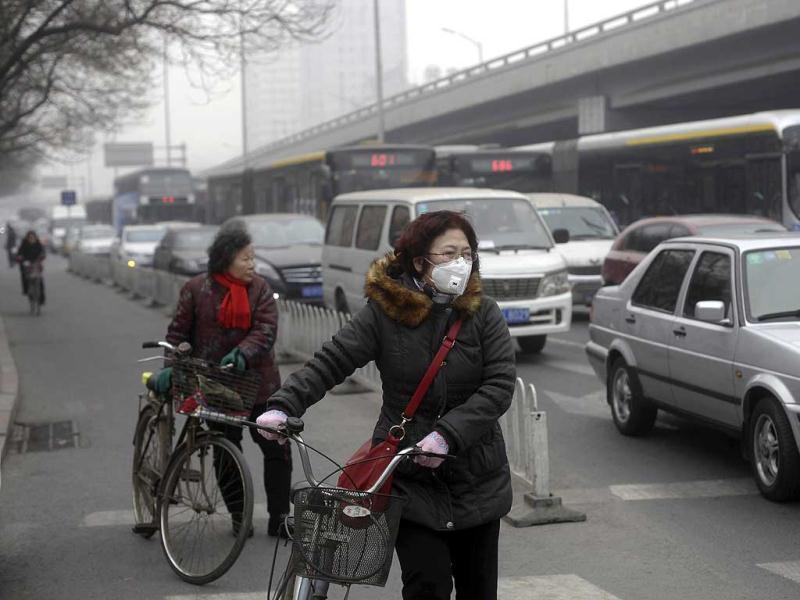 A woman (C) wearing a mask stands besides her bicycle as vehicles stop at a traffic junction on a busy street amid thick haze in Beijing February 25, 2014. Reuters/Barry Huang