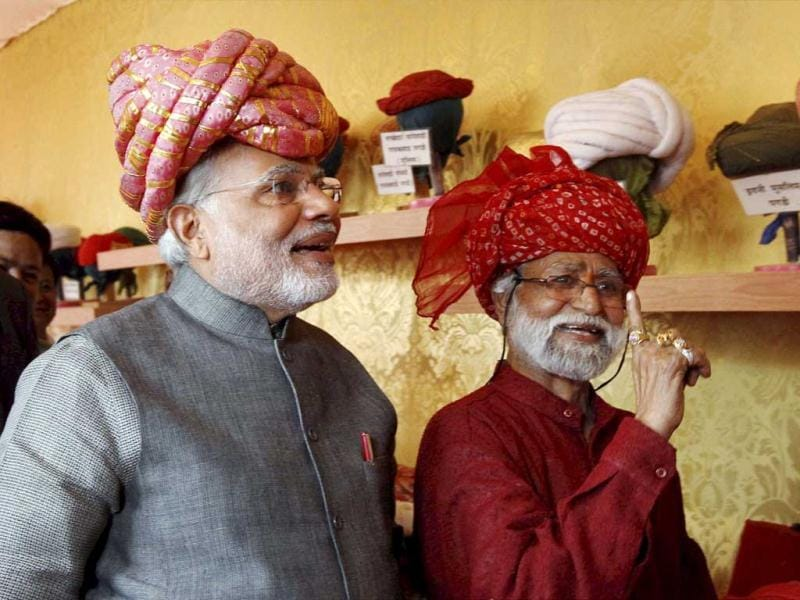 Gujarat Chief Minister and BJP's PM candidate Narendra Modi wears a turban at a stall during inauguration of five-day long handicraft exhibition in Ahmedabad. (PTI Photo)