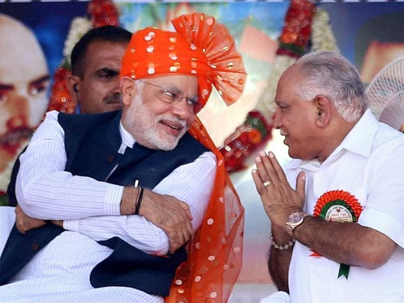 BJP Prime Ministerial Candidate and Gujarat CM Narendra Modi interacts with former CM of the state B.S Yeddyurappa at a rally in Davangere, Karnataka. PTI Photo