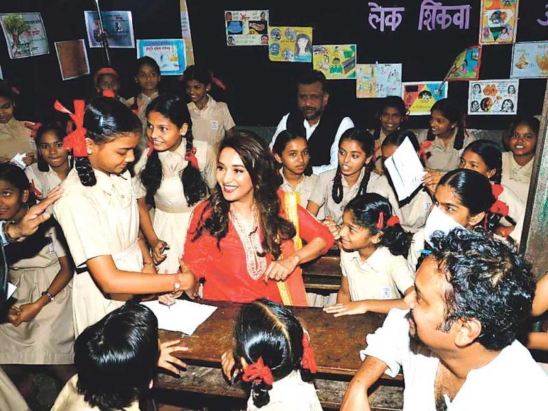 Madhuri Dixit Nene interacts with schoolgirls at a social awareness event in Mumbai.