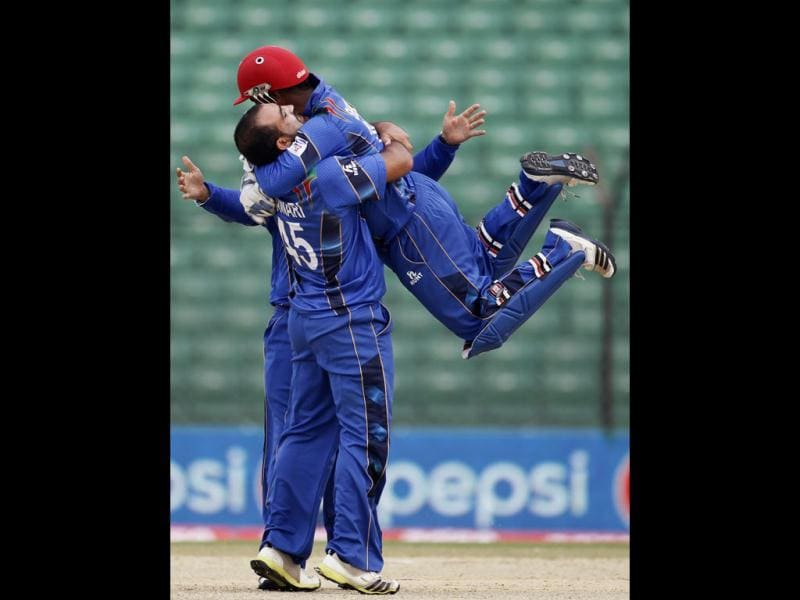 Afghanistan's wicketkeeper Mohammad Shahzad (R) congratulates bowler Samiullah Shenwari (L) as he dismissed Pakistan's Sohaib Maqsood during their Asia Cup match in Fatullah. (Reuters Photo)