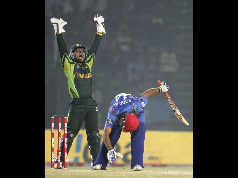 Afghanistan's Noor Ali Zadran tries to play a ball as Pakistan's wicketkeeper Umar Akmal (L) appeals for his dismissal during their Asia Cup 2014 match in Fatullah. (Reuters Photo)