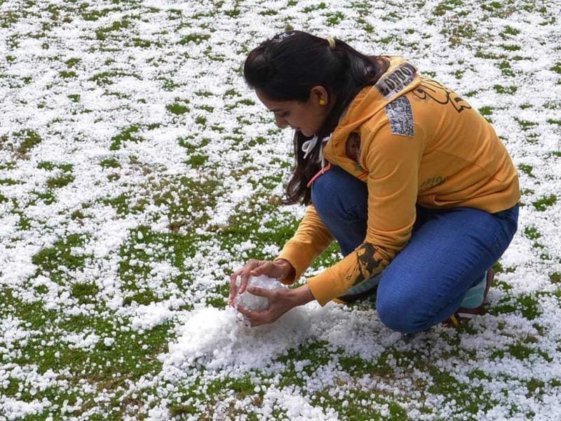 An Indian youth collects hail following a storm in Amritsar. Amritsar experienced a hailstorm as temepratures dipped across the region. (AFP Photo)